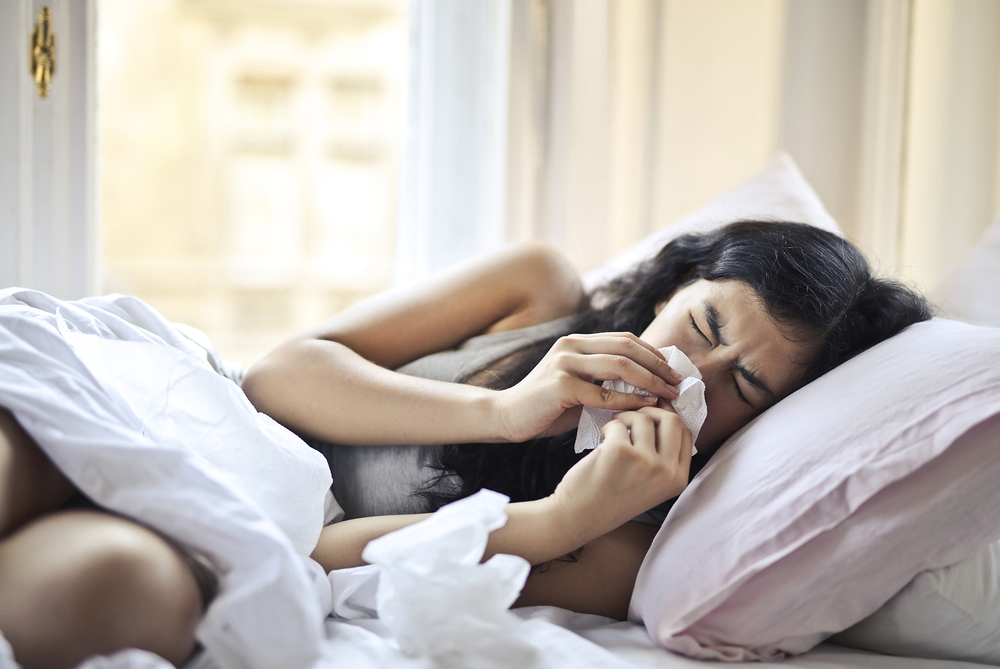 How to Prevent Mold - woman sneezing in bed